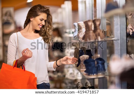 Smiling attractive young women shopping at shoes store - stock photo