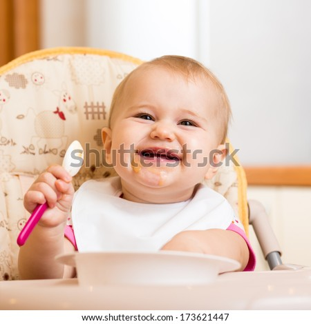 smiling baby eating food on kitchen - stock photo