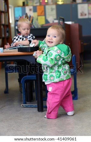 Smiling baby girl and elder brother in library - stock photo