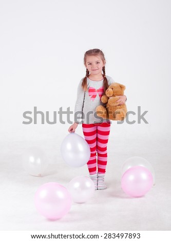 Smiling baby girl holding teddy bear and air balloons in room over white. Isolated. Pajamas party. Childhood. Playful. - stock photo