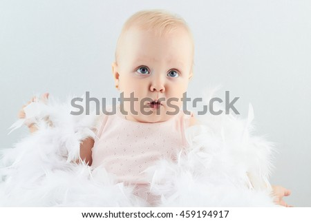 smiling baby girl in feathers. little funny child.newborn - stock photo