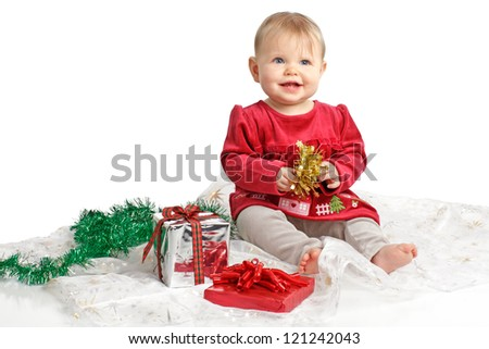 Smiling baby girl in red velvet dress and gray stretch pants holds shiny gold bow. She sits near wrapped holiday gifts and green garland. Isolated/cut out, white background, horizontal, copy space. - stock photo