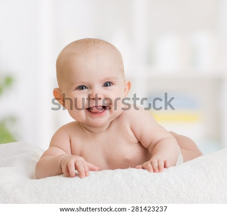 smiling baby girl lying on towel - stock photo