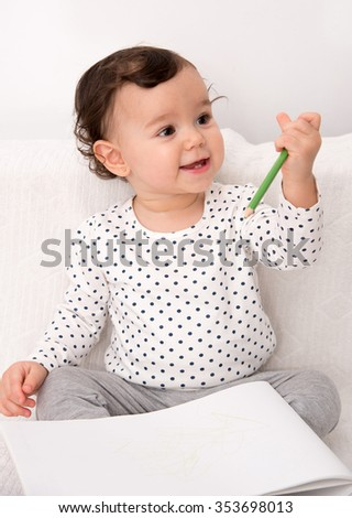 Smiling baby girl sitting on the bed and drawing with a colored pencil on the paper - stock photo