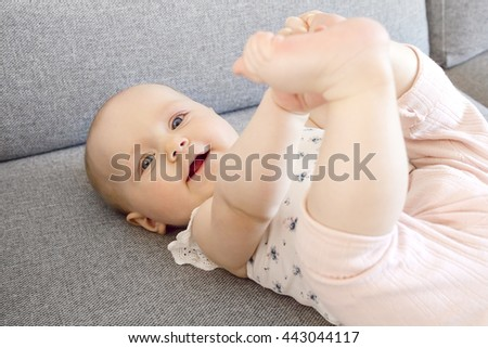 Smiling baby girl with blue eyes playing on the sofa - stock photo