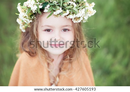 Smiling baby girl 3-4 year old wearing flower wreath outdoors. Looking at camera.  - stock photo