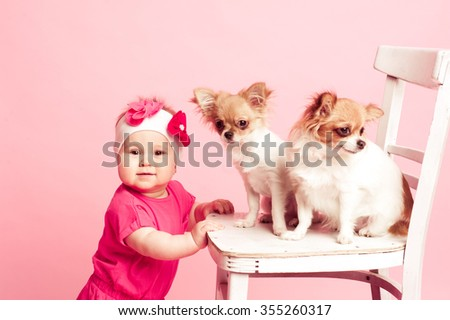 Smiling baby girl 1 year old with two puppies over pink. Looking at camera.  - stock photo
