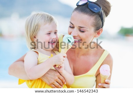 Smiling baby giving mother ice cream - stock photo
