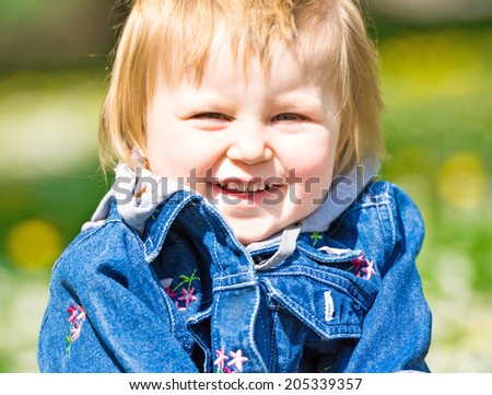 Smiling baby in field of flowers - stock photo