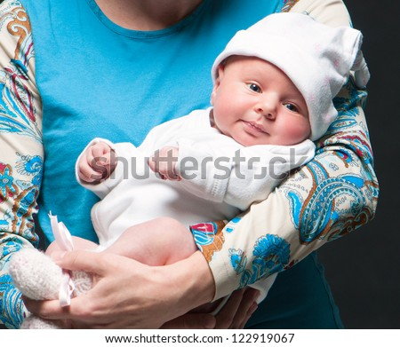 smiling baby in mother's hands - stock photo