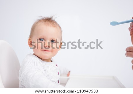 Smiling baby looking at the camera while being fed against a grey background - stock photo