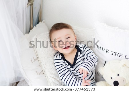 smiling baby lying on the bed with a teddy bear - stock photo