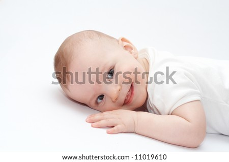 smiling baby lying on the floor - stock photo
