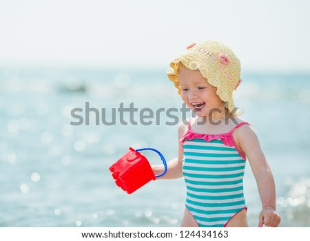 Smiling baby playing with pail on seashore - stock photo