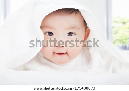 smiling baby smiling under a white blanket or towel - stock photo