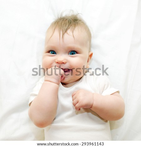 Smiling baby sucking his finger on a white bed. - stock photo