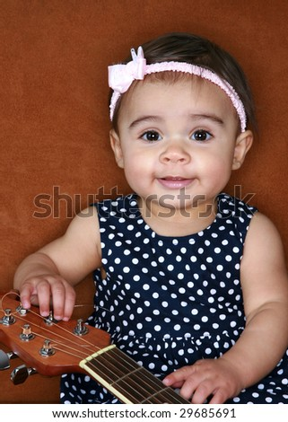 Smiling baby with guitar - stock photo