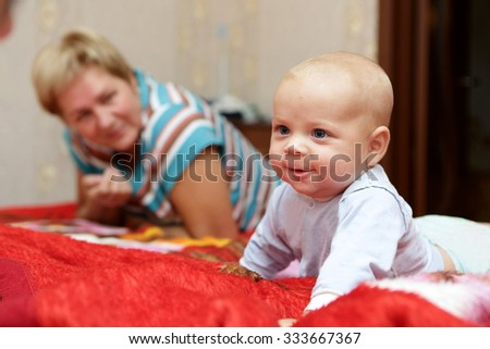 Smiling baby with his grandmother on a bed - stock photo