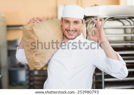 Smiling baker holding bag of flour in the kitchen of the bakery - stock photo