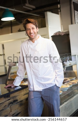 Smiling baker leaning on counter at the bakery - stock photo