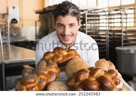 Smiling baker showing board of breads in the kitchen of the bakery - stock photo