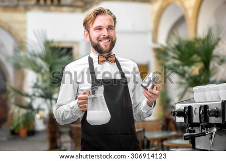Smiling barista in uniform holding milk pitcher and jar filled with milk standing near the coffee machine in the cafe - stock photo