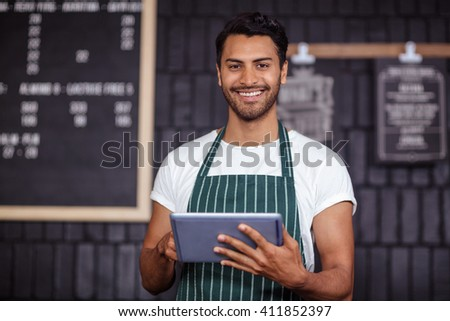 Smiling barista using tablet and looking at the camera in the bar - stock photo