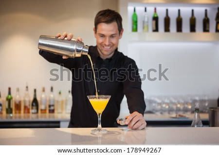 Smiling bartender pouring yellow cocktail into glass at the bar - stock photo