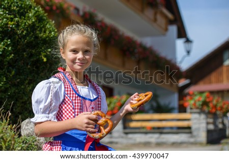 Smiling  bavarian girl holding a pretzel in hands on the farm in Germany . - stock photo