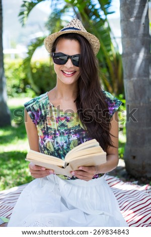 Smiling beautiful brunette sitting and reading a book with palm tree behind her - stock photo