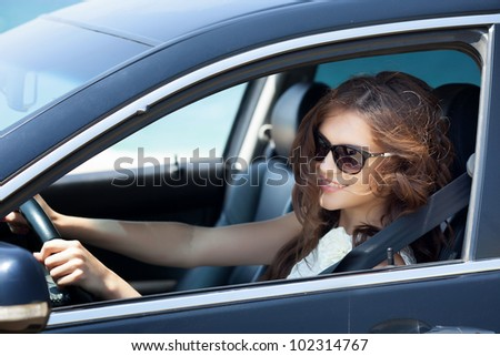 Smiling beautiful brunette woman driving a car - stock photo