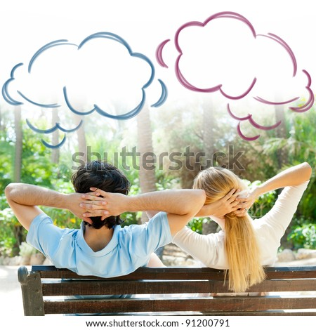 Smiling beautiful couple sitting on a bench at summer park and dreaming about something - stock photo