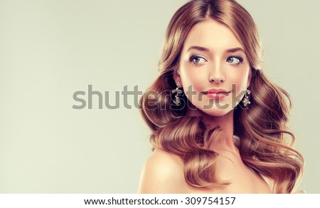 Smiling Beautiful girl brown hair with an elegant hairstyle , hair wave ,curly    with earrings  - stock photo