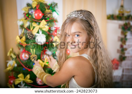 smiling beautiful girl decorates the Christmas tree. Portrait of a beautiful girl with long hair in a gold dress near Christmas tree - stock photo