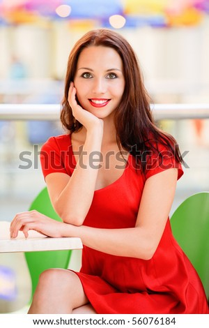 Smiling beautiful girl in red dress sits at table in cosy cafe. - stock photo
