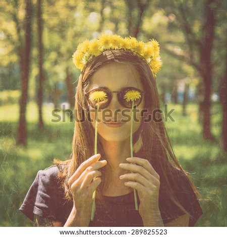 Smiling beautiful girl in wreath of yellow dandelions closed her eyes with dandelions in summer park, concept of happiness and summer mood. Image with old textured effect - stock photo