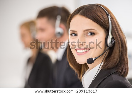 Smiling beautiful lady working at call center with colleagues in office. - stock photo