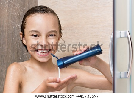 Smiling beautiful little girl bathing under a shower at home - stock photo