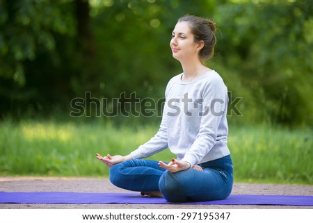 Smiling beautiful sporty young woman sitting cross legged in Ardha Padmasana, half lotus posture on blue mat on the street in park alley with fingers in jnana mudra, meditating, breathing - stock photo