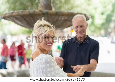Smiling beautiful tanned woman laughing as she turns to look at the camera while holding onto her husbands hands - stock photo