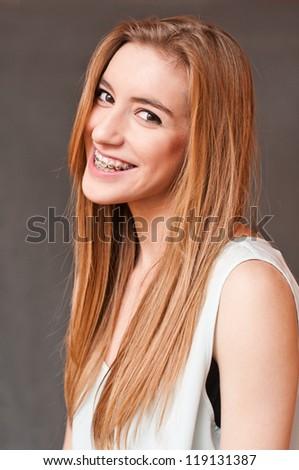 smiling beautiful teenager wearing braces - stock photo