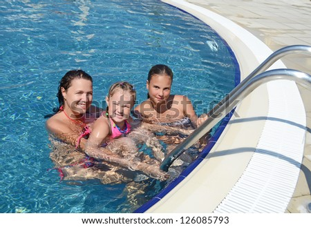 Smiling beautiful woman and her daughter have a fun in pool outdoor - stock photo