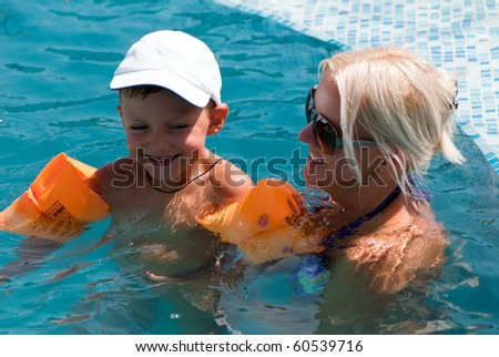 Smiling beautiful woman and little boy bathes in pool - stock photo