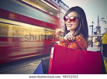 Smiling beautiful woman carrying some shopping bags with londoner street in the background - stock photo