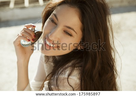 Smiling beautiful woman holding bottle of perfume and smelling aroma. horizontal shot - stock photo