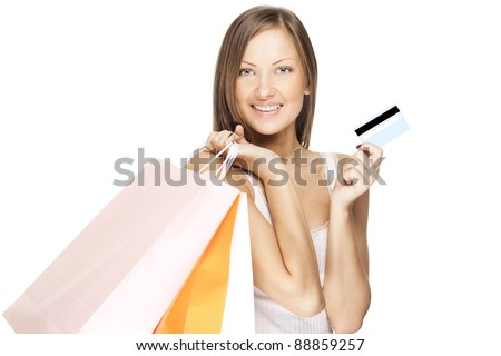 smiling beautiful woman holding shopping bags and credit card - stock photo