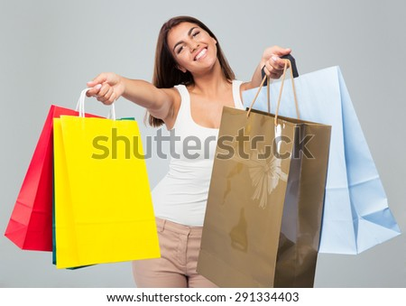 Smiling beautiful woman holding shopping bags over gray background. Looking at camera - stock photo