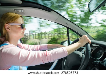 Smiling beautiful woman in sunglasses driving at high speed car with panoramic windshield. Internal stock photo with low shutter speed and blurred in motion natural background. - stock photo