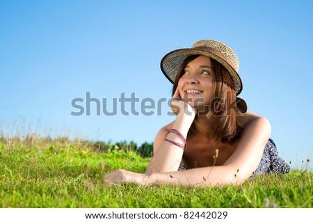 Smiling beautiful woman laying on grass - stock photo