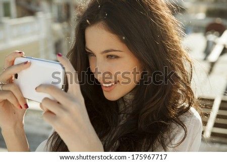 Smiling beautiful woman playing with her smartphone. horizontal outdoors shot. - stock photo